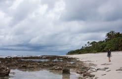 Eine Frau mit einem Rucksack gehend auf einen Strand in Tonga stockfotos
