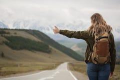 Eine Frau mit einem Rucksack und einer Straße, die in den Abstand ausdehnen lizenzfreies stockbild