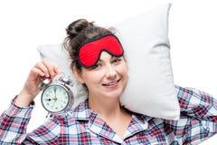 Eine Frau mit einem Wecker und einem Kissen Lizenzfreie Stockfotos