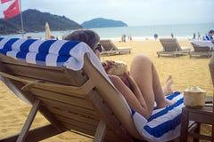 Eine Frau mit einer Kokosnuss, die auf den Ruhesesseln auf dem Strand liegt Stockfotos