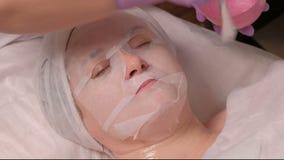 Eine Frau mit einer kosmetischen Maske liegt auf dem Verfahren in dem Gesundheitszentrum Ein Berufscosmetologist in den lila Hand stock footage