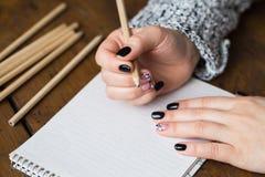 Eine Frau mit einer schönen Maniküre zeichnet in ein Notizbuch Stockbilder
