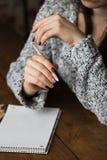Eine Frau mit einer schönen Maniküre zeichnet in ein Notizbuch Lizenzfreies Stockfoto