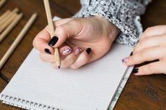 Eine Frau mit einer schönen Maniküre zeichnet in ein Notizbuch Stockfotos
