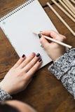 Eine Frau mit einer schönen Maniküre zeichnet in ein Notizbuch Stockbild