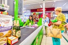 eine Frau mit gekauften Produkten ist am Schreibtisch des Kassierers im Supermarkt Text auf russisch: Katzenstreu, Pastete lizenzfreie stockfotos