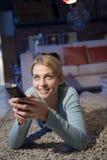 Eine Frau mit ihrer Fernsehentfernten station Stockfotografie