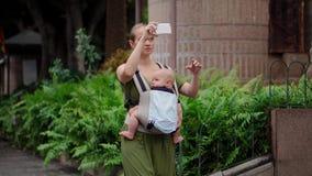 Eine Frau mit Reisen eines Babys auf der Insel, die ein Kind in einem Riemen sitzt stock video