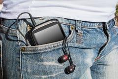 Eine Frau mit Smartphone und Kopfhörer in ihrer Hosen-Tasche Lizenzfreie Stockbilder
