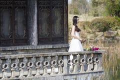 Eine Frau mit weißem Hochzeitskleid tragen Brautblumenstraußstand in einem Kloster in shui BO-Park von Shanghai Lizenzfreie Stockbilder