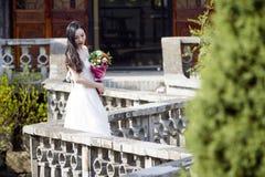 Eine Frau mit weißem Hochzeitskleid tragen Brautblumenstraußstand in einem Kloster in shui BO-Park von Shanghai Lizenzfreie Stockfotografie