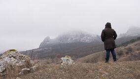 Eine Frau nähert sich dem Fuß des Berges und stoppt stock video footage
