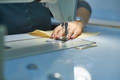 Eine Frau näht auf einer elektrischen Nähmaschine stockbild