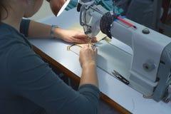 Eine Frau näht auf einer elektrischen Nähmaschine lizenzfreie stockfotografie