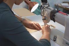 Eine Frau näht auf einer elektrischen Nähmaschine lizenzfreie stockbilder