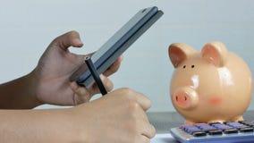 Eine Frau nimmt Kenntnisse und benutzt einen Smartphone mit einem Tropfen des Geldes in ein Sparschwein stock video footage