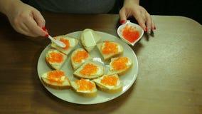 Eine Frau nimmt roten Kaviar von einem Löffel von Iornitsa und verbreitet Butter auf einem Canape mit Butter stock video