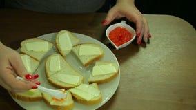 Eine Frau nimmt roten Kaviar von einem Löffel von Iornitsa und verbreitet Butter auf einem Canape mit Butter stock footage