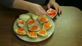 Eine Frau nimmt roten Kaviar von einem Löffel von Iornitsa und verbreitet Butter auf einem Canape mit Butter stock video footage
