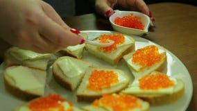 Eine Frau nimmt roten Kaviar von einem Löffel von Iornitsa und verbreitet Butter auf einem Canape mit Butte stock video