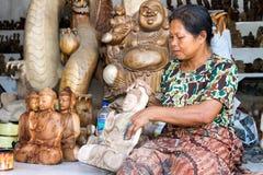 Eine Frau poliert hölzernen Buddha Stockbilder