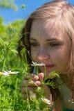 Eine Frau riecht auf Blumen im Park lizenzfreie stockbilder