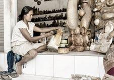 Eine Frau sättigt mit Fleck hölzerner Buddha Lizenzfreie Stockfotografie