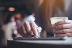 Eine Frau ` s Hand, die Tabletten-PC beim Halten der Kaffeetasse mit Unschärfehintergrund im Café zeigt, berührt und verwendet Lizenzfreie Stockbilder