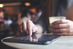 Eine Frau ` s Hand, die Tabletten-PC beim Halten der Kaffeetasse mit Unschärfehintergrund im Café zeigt, berührt und verwendet Lizenzfreies Stockfoto