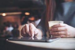Eine Frau ` s Hand, die Tabletten-PC beim Halten der Kaffeetasse mit Unschärfehintergrund im Café zeigt, berührt und verwendet Stockbild