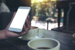 Eine Frau ` s Hand, die weißen Handy mit leerem Tischplattenschirm mit Kaffeetassen auf Holztisch im Café hält Stockfotografie