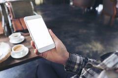Eine Frau ` s Hand, die weißen Handy mit leerem Tischplattenschirm mit Kaffeetassen auf Holztisch im Café hält Lizenzfreie Stockfotografie