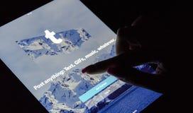 Eine Frau ` s Hand ist Touch Screen auf Tablette iPad, das nachts mit Internet-Service Tumblr am Schirm Pro ist Tumblr microblogg stockbilder