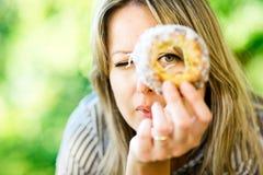Eine Frau schaut durch Kuchen Trdelnik lizenzfreie stockfotografie