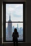 Eine Frau schaut heraus über im Stadtzentrum gelegenen Manhattan-Skylinen mit dem Empire State Building, New York City Stockfotos