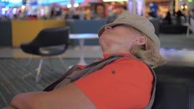 Eine Frau schlafend in den Flughafenstühlen, die auf eine verzögerte flache Abfahrt warten stock video