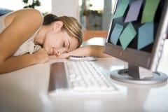 Eine Frau schlafend an ihrem Computer Lizenzfreie Stockfotografie
