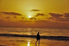 Eine Frau schlendert entlang den Ozean Stockbild