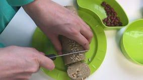 Eine Frau schneidet eine Wurst in Teile von einer Mischung mit zerquetschten Erdnüssen, Sonnenblumensamen und Honig Halva, zu Hau stock footage