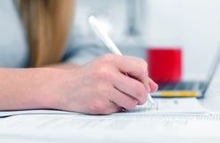Eine Frau schreibt beim Sitzen an einem Tisch in ein Büro oder in ein Klassenzimmer Das Mädchen füllt die Dokumente am Arbeitspla lizenzfreie stockbilder