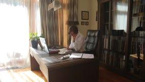 Eine Frau schreibt in ein Notizbuch an ihrem Schreibtisch in ihrem Innenministerium stock footage
