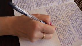Eine Frau schreibt handgeschriebenen Text mit einem Kugelschreiber in ein Notizbuch stock video footage