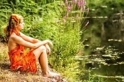 Eine Frau sitzt auf der Bank des Flusses, der weit weg schaut Lizenzfreie Stockfotos
