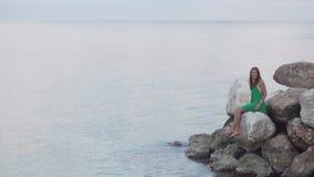 Eine Frau sitzt auf Felsen nahe dem Meer stock footage