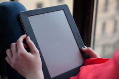 Eine Frau sitzt am Fenster und benutzt ein eBook Unbelegter Bildschirm Stockbild