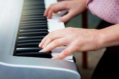 Eine Frau spielt ein Klavier Hände des Musikers auf dem Klavier keys_ lizenzfreie stockfotografie