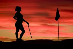 Eine Frau spielt Golf gegen einen leuchtenden Sonnenuntergang Lizenzfreies Stockfoto