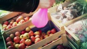 Eine Frau sprüht Frucht auf einem Straßenmarkt stock footage