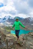 Eine Frau steht gegen einen Hintergrund des Schnee-mit einer Kappe bedeckten Berges Lizenzfreie Stockbilder