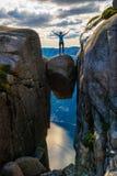 Eine Frau steht am Rand eines Flussstein Kjeragbolten-stuc stockfoto